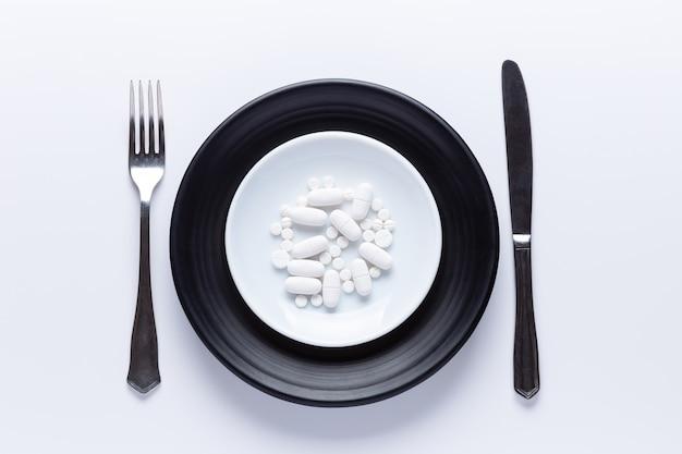 Teller mit pillen mit messer und gabel. isoliert. draufsicht, pharmakologie-konzept. weiße pillen