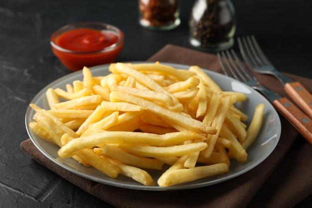 Teller mit pommes frites, serviette, roter sauce, gabeln auf schwarz. nahansicht