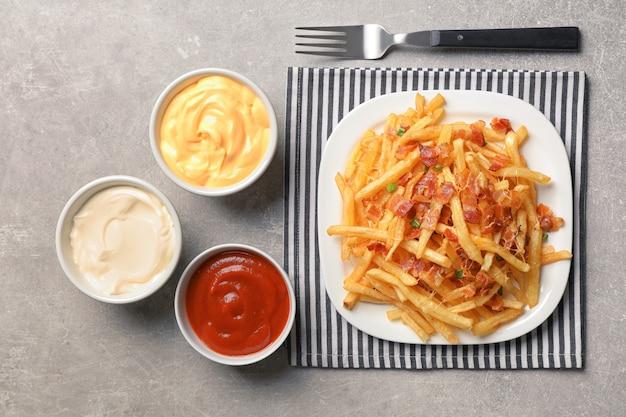 Teller mit pommes frites und speck auf dem tisch
