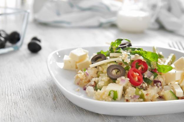 Teller mit quinoa-salat auf holztisch
