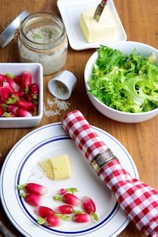 Teller mit radieschen, butter und salat auf einem rustikalen tisch