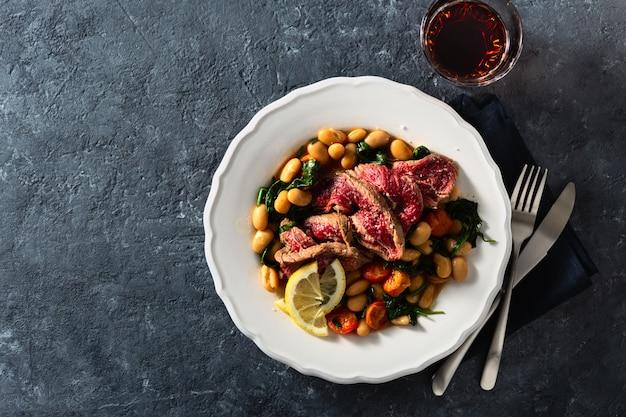 Teller mit rindersteak mit weißen bohnen, spinat, tomaten und einem glas rotwein
