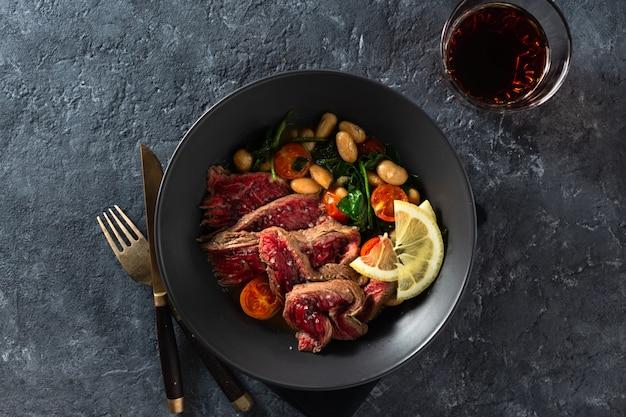 Teller mit rindersteak mit weißen bohnen, spinat und tomaten mit einem glas rotwein