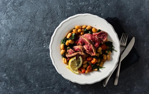 Teller mit rindersteak mit weißen bohnen, spinat und tomaten