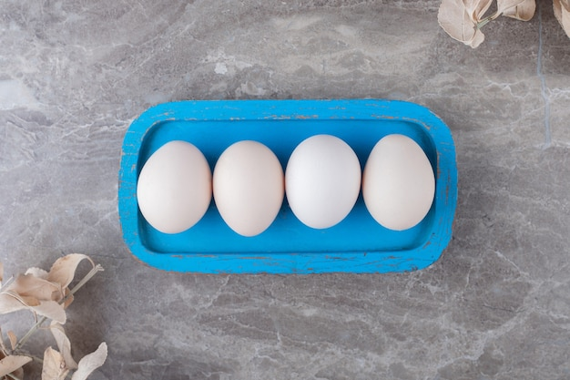 Teller mit rohen eiern auf marmorhintergrund.