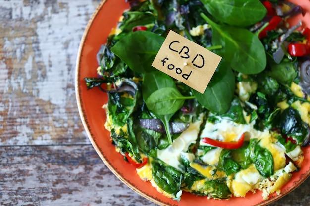 Teller mit rührei mit spinat und gemüse.