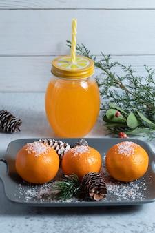 Teller mit saftigen mandarinen, dekoriert mit pulver und tannenzapfen und einem glas saft. hochwertiges foto