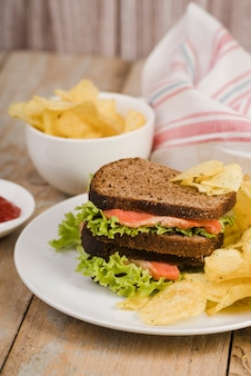 Teller mit sandwich neben schüssel mit pommes