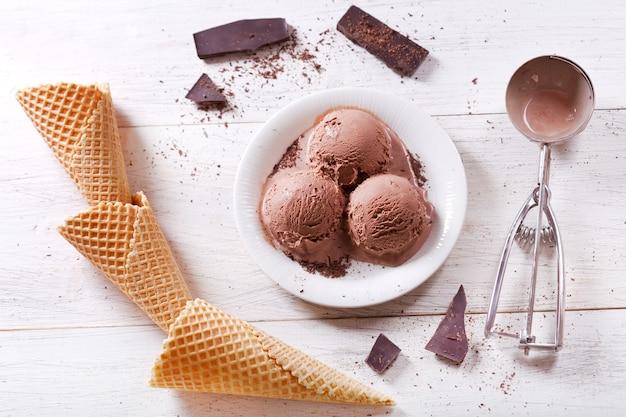 Teller mit schokoladeneisschaufeln und waffeltüten auf holztisch, draufsicht