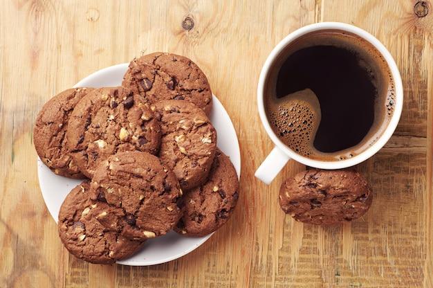 Teller mit schokoladenkeksen und tasse heißen kaffees auf altem holztisch