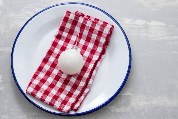 Teller mit serviette und weihnachtsspielzeug auf keramikhintergrund