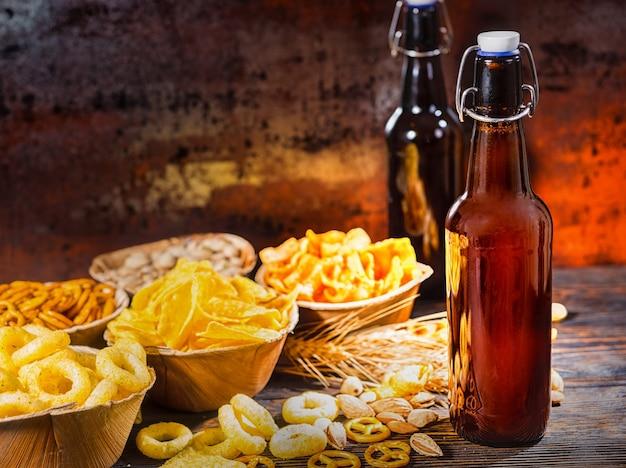 Teller mit snacks in der nähe von zwei flaschen bier, weizen, verstreuten nüssen und brezeln auf dunklem holzschreibtisch. lebensmittel- und getränkekonzept