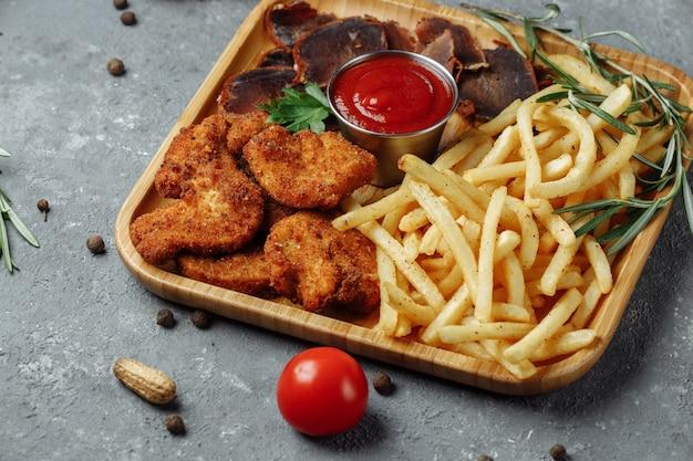 Teller mit snacks. panierte hühnernuggets, bratkartoffeln und jamon.