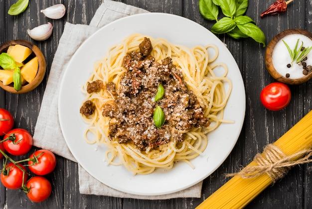 Teller mit spaghetii bolognese auf dem schreibtisch