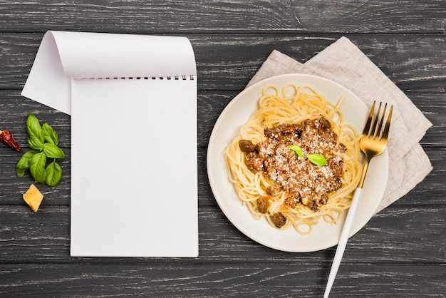 Teller mit spaghetii bolognese und notizbuch
