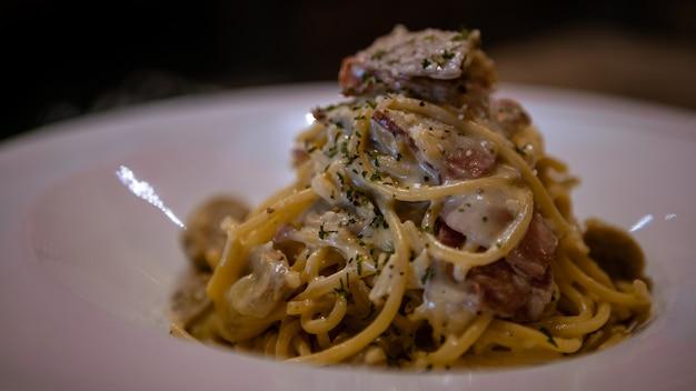 Teller mit spaghetti alla carbonara auf dem tisch des restaurants. weißer teller mit typisch italienischem nudelrezept mit speck, ei, sahnesauce und parmesankäse. traditionelle küche italiens.