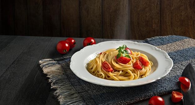Teller mit spaghetti, tomaten und basilikum auf dunklem holzhintergrund. heiße spaghetti mit dampf. platz kopieren