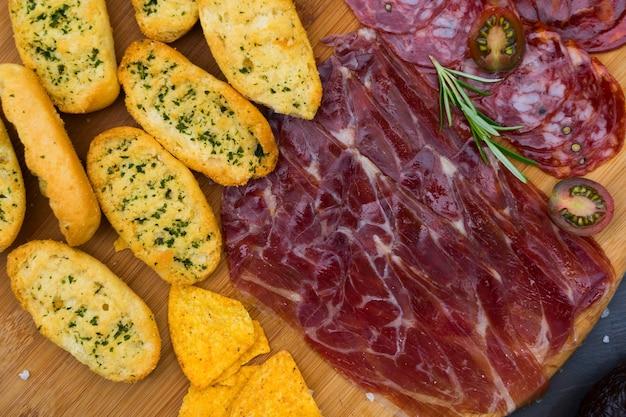Teller mit spanischem jamon-schinken und chorizo-tapas, picknicktisch-draufsicht