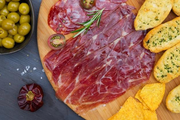 Teller mit spanischem jamon und chorizo-tapas, picknicktisch