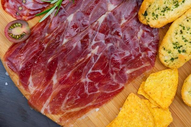 Teller mit spanischem schinken und chorizo-tapas, picknicktisch