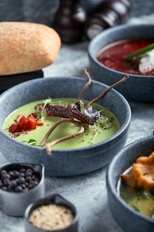 Teller mit spargelsuppe mit tintenfisch, ein teller traditioneller borschtsch mit saurer sahne, ein teller mit pilzsuppe