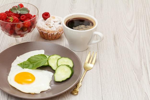 Teller mit spiegelei, frisch geschnittener gurke und basilikumblatt, gabel, tasse schwarzem kaffee, muffin und glasschüssel mit frischen himbeeren auf grauem holzhintergrund
