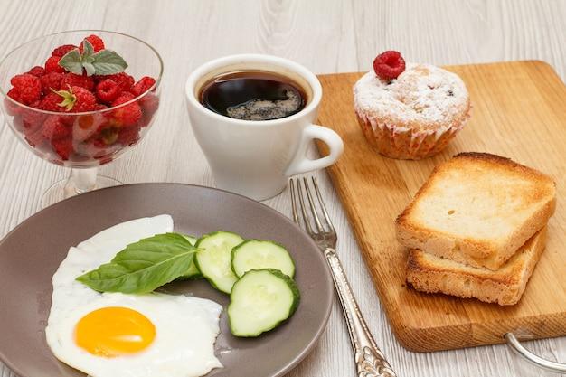 Teller mit spiegelei, frisch geschnittener gurke und basilikumblatt, glasschüssel mit frischen himbeeren, tasse schwarzem kaffee, gabel, muffin und toast auf holzbrett.