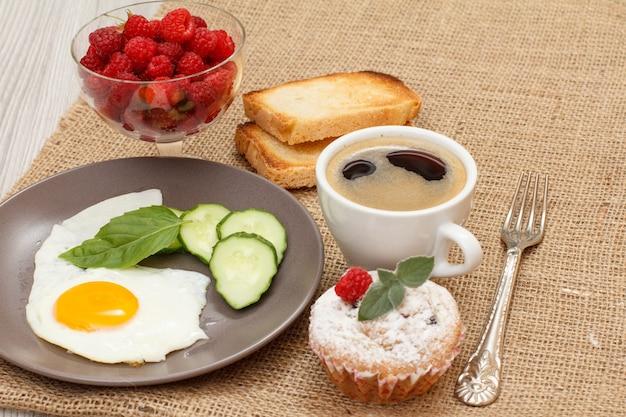 Teller mit spiegelei, frisch geschnittener gurke und basilikumblatt, muffin, tasse schwarzem kaffee, gabel, toast und glasschüssel mit frischen himbeeren auf dem mit sacktuch bedeckten tisch