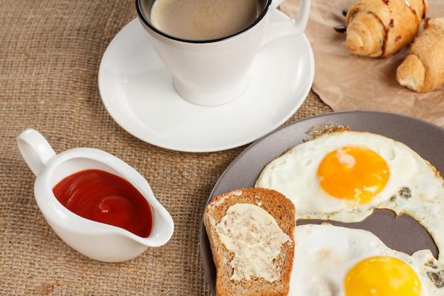 Teller mit spiegeleiern und toast mit butter, croissants, tasse schwarzem kaffee und ketchup in einer sauciere auf dem mit sacktuch bedeckten tisch.