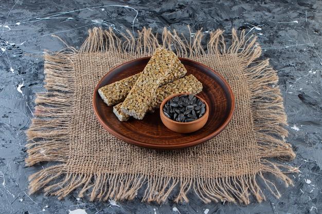 Teller mit spröden bonbons mit sonnenblumenkernen auf marmoroberfläche.