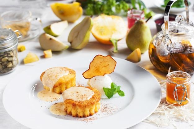 Teller mit süßen cupcakes und eisbällchen auf dem tisch.