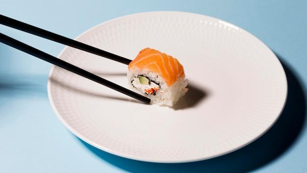 Teller mit sushi-rolle und essstäbchen