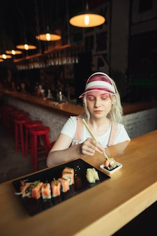 Teller mit sushi-rollen im restaurant mit frau, die essstäbchen hält