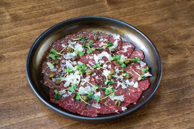 Teller mit trockenfleisch mit mikrogrün, kapern und parmesan. servieren von fleischgerichten und vorspeisen beim bankett. den tisch bedienen.