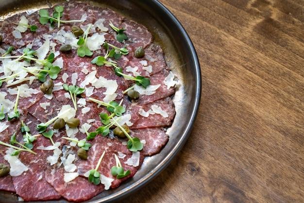 Teller mit trockenfleisch mit mikrogrün, kapern und parmesan.