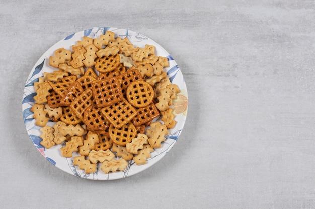 Teller mit verschiedenen gesalzenen crackern auf stein.