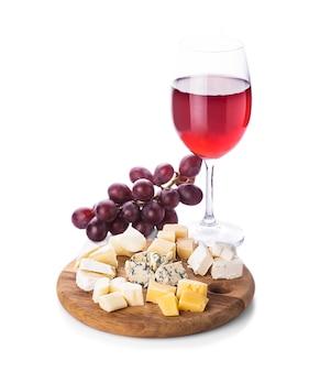 Teller mit verschiedenen käsesorten, trauben und glas wein, isoliert auf weiß
