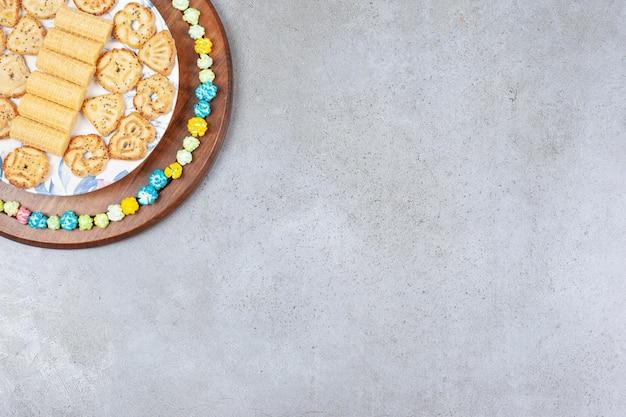 Teller mit verschiedenen keksen, umgeben von popcorn-süßigkeiten auf holzbrett auf marmorhintergrund.