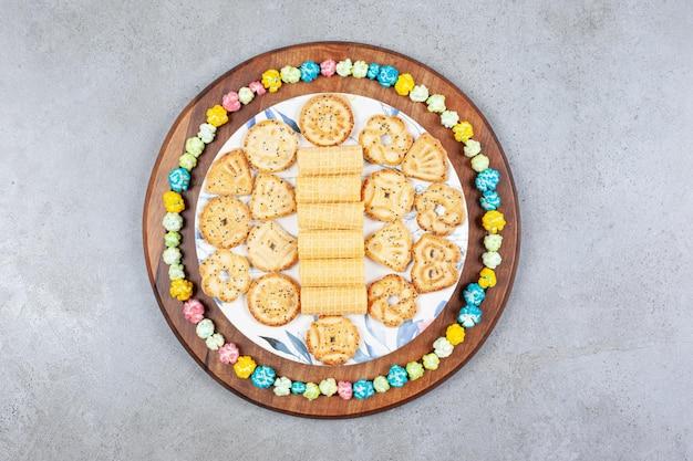 Teller mit verschiedenen keksen, umgeben von popcorn-süßigkeiten auf holzbrett auf marmoroberfläche.