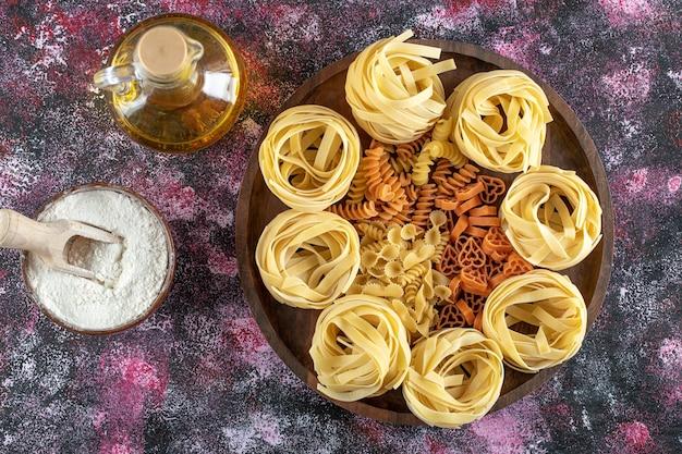 Teller mit verschiedenen makkaroni mit schüssel mehl und öl.