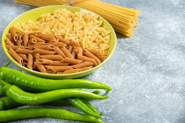 Teller mit verschiedenen nudeln, chilischoten und spaghetti auf marmorhintergrund.