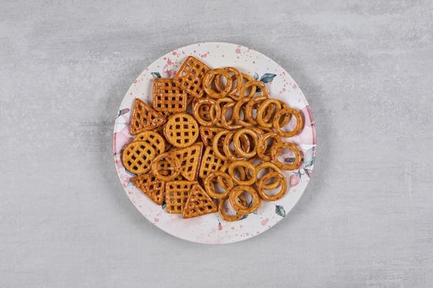 Teller mit verschiedenen salzigen crackern auf stein.