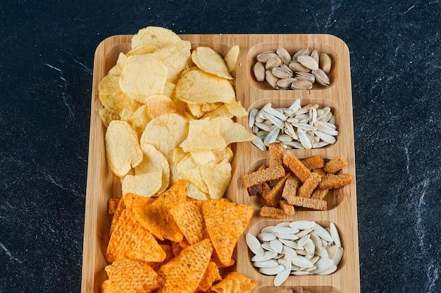 Teller mit verschiedenen snacks auf einem dunklen tisch