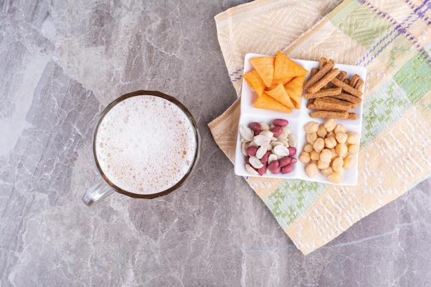 Teller mit verschiedenen snacks und bieren auf marmoroberfläche. foto in hoher qualität