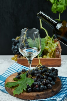 Teller mit verschiedenen trauben und ein glas wein auf weißem tisch mit weinflasche