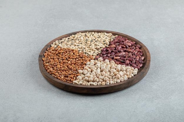Teller mit verschiedenen trockenen erbsen und bohnen auf marmoroberfläche.