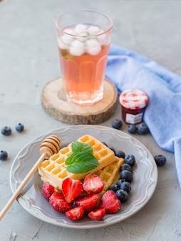 Teller mit waffeln, verziert mit honig und frischen beeren und glas frischem roten fruchtsaft auf grauer steinoberfläche