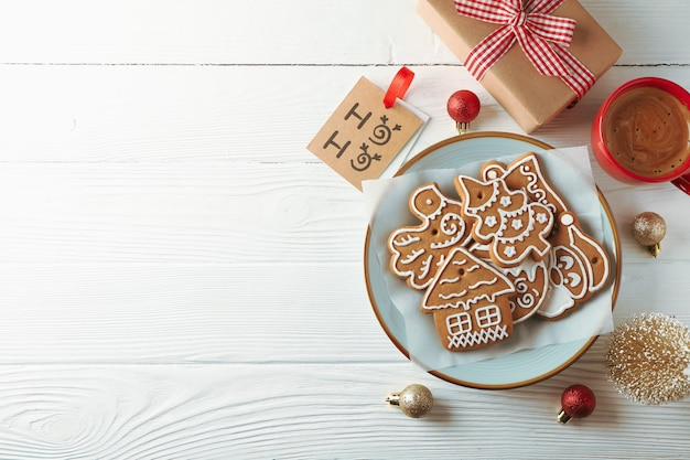 Teller mit weihnachtsplätzchen, spielzeug und kaffee auf weißem holz, platz für text. draufsicht