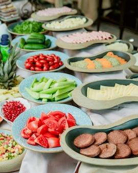 Teller mit würstchen, käsetomaten und gurken
