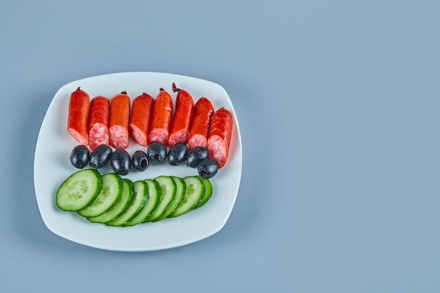 Teller mit würstchen oliven und gurkenscheiben auf blau